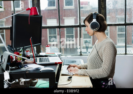 Young female designer wearing headphones in design studio - Stock Photo