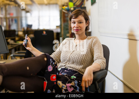 Young female designer with feet up in design studio - Stock Photo