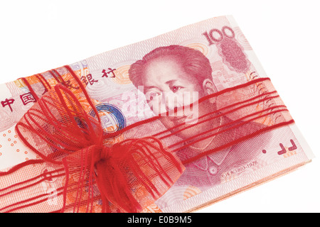 Chinese yuan of bank notes with a red loop, Chinesische Yuan Banknoten mit einer roten Schleife - Stock Photo