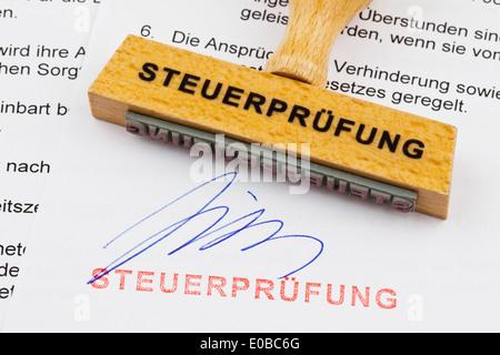 'A stamp of wood lies on a document. German label; tax check', 'Ein Stempel aus Holz liegt auf einem Dokument. Deutsche - Stock Photo