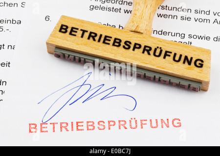 A stamp of wood lies on a document. German label: Audit of operating results, Ein Stempel aus Holz liegt auf einem - Stock Photo