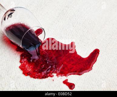 A glass with red wine was buried on a carpet. Damage for assurance., Ein Glas mit Rotwein wurde auf einem Teppich - Stock Photo