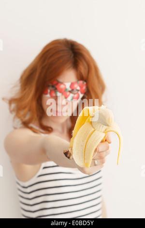 Superhero girl wearing mask with strawberries aiming with banana gun - Stock Photo