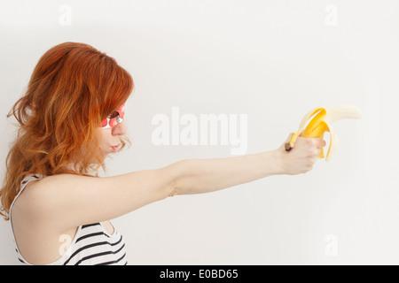 Superhero girl wearing mask with strawberries and holding banana gun - Stock Photo