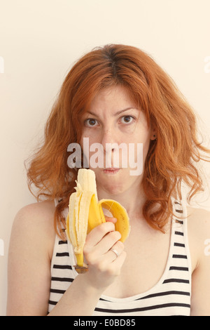Young Woman Eating a Banana - Stock Photo