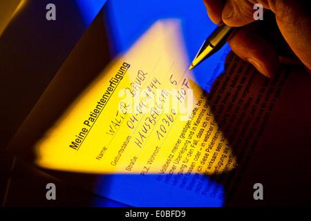 A patient's possession is written by a patient., Eine Patientenverfuegung wird von einem Patienten geschrieben. - Stock Photo