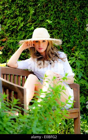 Young woman in the garden relaxing. With a solar hat, Junge Frau im Garten beim entspannen. Mit einem Sonnenhut - Stock Photo