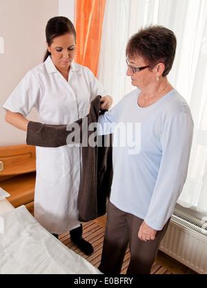 a nurse with geriatric care of senior citizens in the old people's home, eine Pflegerin bei Altenpflege von Senioren - Stock Photo