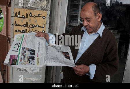 May 8, 2014 - Deir Al-Balah, Gaza Strip, Palestinian Territory - A Palestinian man reads a copy of the Palestinian Al-Ayyam newspaper in Deir al-Balah in the center of Gaza Strip, on May 8, 2014. The Palestinian daily which is edited and printed in the West Bank city of Ramallah has been allowed by the Hamas to be distributed in the Gaza strip for the first time in seven years, after the Islamist movement and the western-backed Palestinian Authority signed a surprise reconciliation agreement on April 23 in a bid to end years of bitter and sometime bloody rivalry (Credit Image: © Ashraf Amra/A
