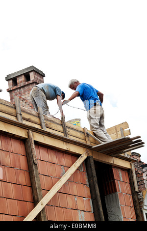 Two construction workers at works on a house roof. - Stock Photo