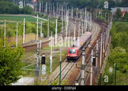 A train for people goes on railroad tracks, Ein Zug fuer Personen faehrt auf Eisenbahnschienen - Stock Photo
