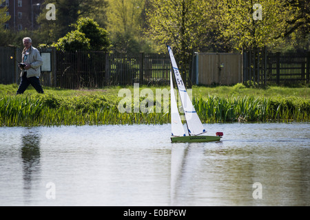 Elderly man sailing his model yacht on Rick Pond, Home Park, Kingston, Surrey, England, UK - Stock Photo