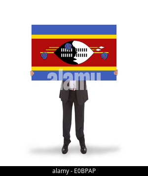 Businessman holding a big card  flag of Swaziland - Stock Photo