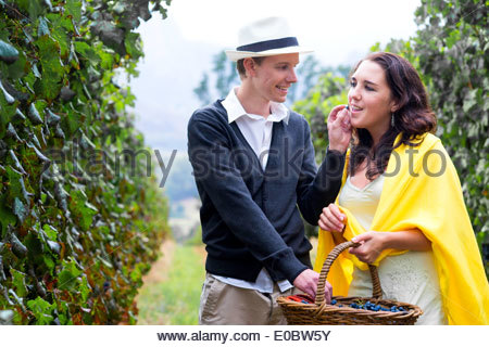 Smiling man feeds grapes to woman in her 20s in a vineyard - Stock Photo