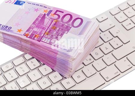A lot of 500 euromoney bank notes lies on a pile. On a computer keyboard, Viele 500 Eurogeld Banknoten liegen auf - Stock Photo