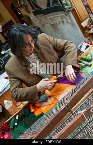 Lisa Trujillo working at loom, Centinela Traditional Arts, Chimayo, New Mexico USA - Stock Photo