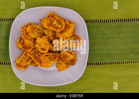 Cappellacci with ragù: Famous dish in Ferrara, pasta stuffed with pumpkin - Stock Photo