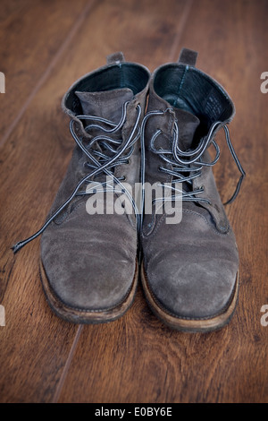 A pair of grey suede man's lace-up boots on a wooden floor. - Stock Photo