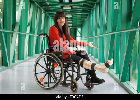 Young woman with gypsum leg sits in a wheel chair, Junge Frau mit Gipsbein sitzt in einem Rollstuhl - Stock Photo