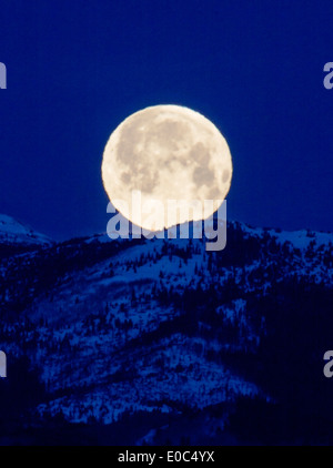 Full moon setting over Rocky Mountains, Salida, Colorado, USA - Stock Photo