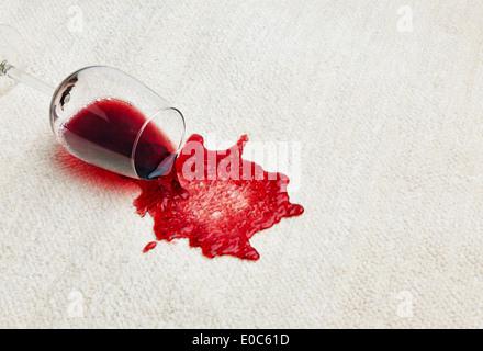 Red wine is tipped out on a carpet. Umgeleertes glass, Roter Wein wird auf einem Teppich ausgeschuettet. Umgeleertes - Stock Photo
