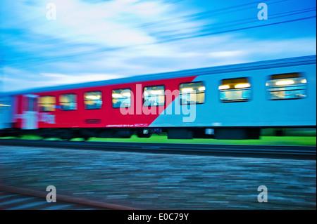 A stopping train goes by the night. Night train with people oeBB, Ein Personenzug faehrt durch die Nacht. Nachtzug - Stock Photo