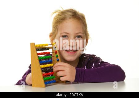 A small school child counts on an abacus., Ein kleines Schulkind rechnet mit einem Abakus. - Stock Photo