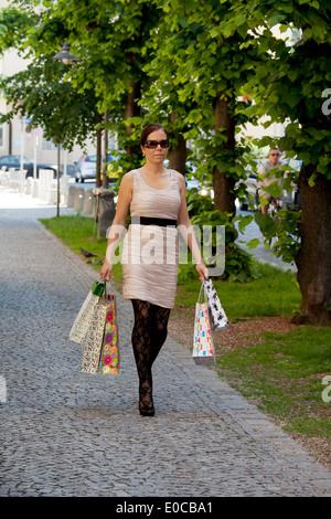 A young woman with shop with carrier bags., Eine junge Frau beim shoppen mit Einkaufstaschen. - Stock Photo