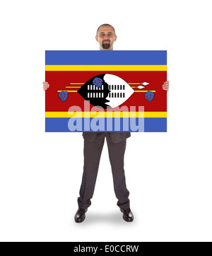 Smiling businessman holding a big card  flag of Swaziland - Stock Photo