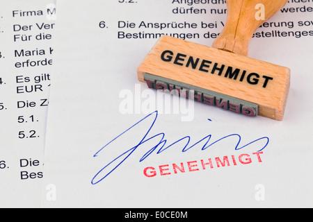 A stamp of wood lies on a document. Label Approved, Ein Stempel aus Holz liegt auf einem Dokument. Aufschrift Genehmigt - Stock Photo