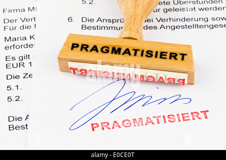A stamp of wood lies on a document. Label Tenured, Ein Stempel aus Holz liegt auf einem Dokument. Aufschrift Pragmatisiert - Stock Photo