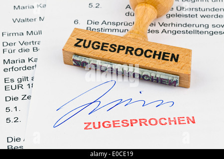 A stamp of wood lies on a document. Label Awarded, Ein Stempel aus Holz liegt auf einem Dokument. Aufschrift Zugesprochen - Stock Photo