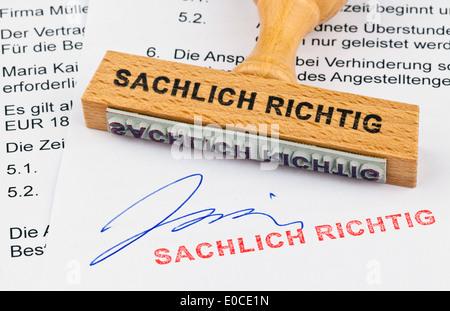 A stamp of wood lies on a document. Label Essentially properly, Ein Stempel aus Holz liegt auf einem Dokument. Aufschrift - Stock Photo
