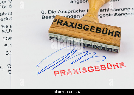A stamp of wood lies on a document. Label Practise fee, Ein Stempel aus Holz liegt auf einem Dokument. Aufschrift - Stock Photo