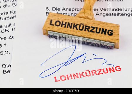 A stamp of wood lies on a document. Label Wage shortening, Ein Stempel aus Holz liegt auf einem Dokument. Aufschrift - Stock Photo