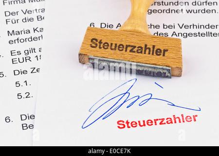A stamp of wood lies on a document. Label Taxpayer, Ein Stempel aus Holz liegt auf einem Dokument. Aufschrift Steuerzahler - Stock Photo