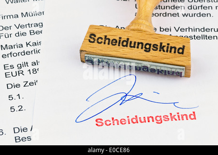 A stamp of wood lies on a document. Label Separation child - Stock Photo