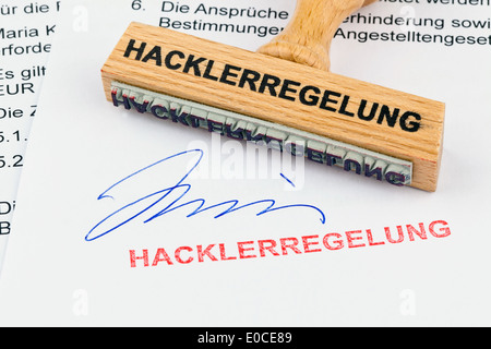 A stamp of wood lies on a document. Label Hacklerregelung, Ein Stempel aus Holz liegt auf einem Dokument. Aufschrift - Stock Photo