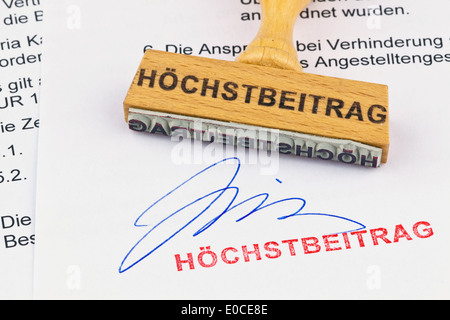 A stamp of wood lies on a document. Label Hoechstbeitrag, Ein Stempel aus Holz liegt auf einem Dokument. Aufschrift - Stock Photo