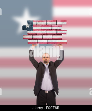 Businessman holding a large piece of a brick wall  flag of Liberia  isolated on national flag - Stock Photo