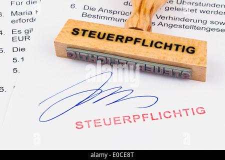 A stamp of wood lies on a document. Label Taxable, Ein Stempel aus Holz liegt auf einem Dokument. Aufschrift Steuerpflichtig - Stock Photo