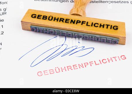 A stamp of wood lies on a document. Label Subject to charges, Ein Stempel aus Holz liegt auf einem Dokument. Aufschrift - Stock Photo