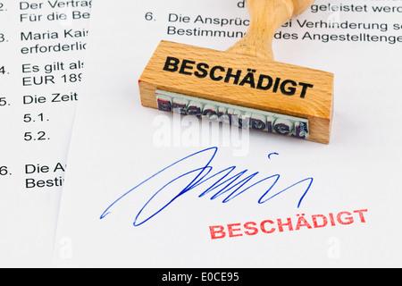 A stamp of wood lies on a document. Label Damaged, Ein Stempel aus Holz liegt auf einem Dokument. Aufschrift Beschaedigt - Stock Photo