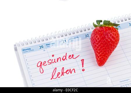 Strawberry and calendar. Good intention to the healthy food, Erdbeere und Kalender. Guter Vorsatz zur Gesunden Ernaehrung - Stock Photo