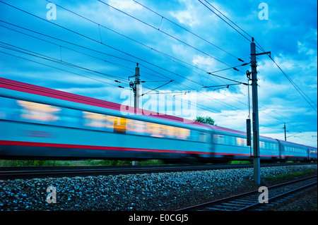 A stopping train goes by the night. Night train with people ? Federal Railway, Ein Personenzug faehrt durch die - Stock Photo