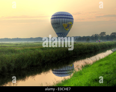 Hot air balloon on the ground in summer landscape in the Northern Netherlands - Stock Photo