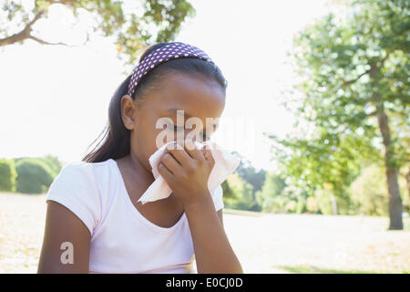 Little girl sitting on grass blowing her nose - Stock Photo