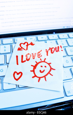 A note slip of paper lies on the keyboard of a computer in memory: I love you - Stock Photo