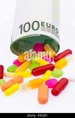 100 euronotes and tablets on wei? ?? to em background., Ein 100 Euroschein und Tabletten auf weiflem Hintergrund. - Stock Photo