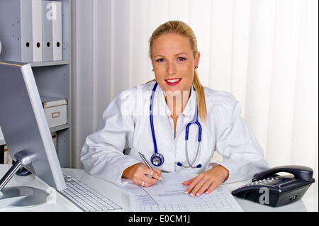 A young doctor with Stethoskop in her medical practise., Eine junge aerztin mit Stethoskop in ihrer Arztpraxis. - Stock Photo